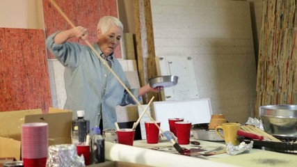 Senior Caucasian woman painting in studio