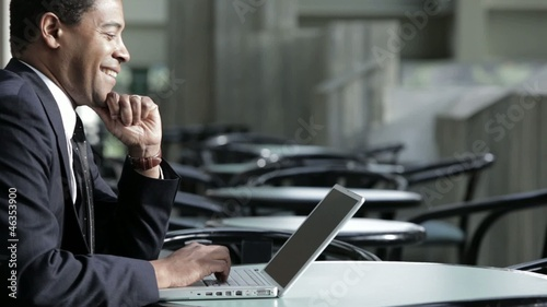 Black businessman using laptop in cafe