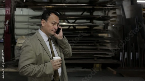 Hispanic factory supervisor talking on cell phone