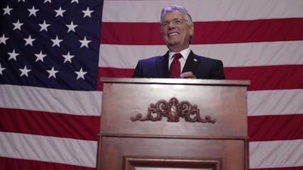 Caucasian politician standing at podium