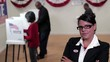 Businesswoman looking at camera in front of row of voters at voting booths