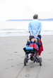 Father pulling disabled son on wheelchair through beach sand