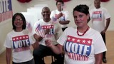 """Group of voters wearing """"vote"""" shirts standing in polling place and waving flags"""