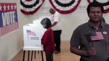 Man waving flag at camera in front of row of voters at voting booths