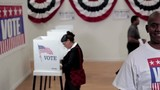 """Man wearing """"vote"""" shirt looking at camera standing in front of row of voters at voting booths"""