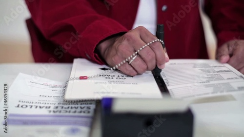 Hispanic voter's hands voting in voting booth