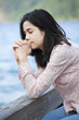 Young teen girl sitting quietly on lake pier, praying