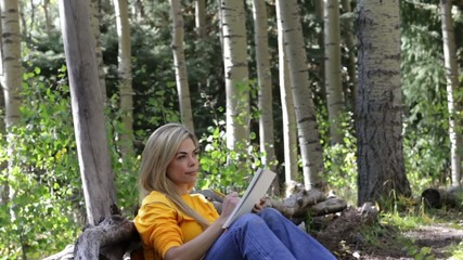 Hispanic woman taking a break from hike to write