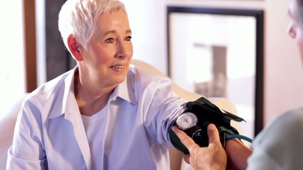 Senior Caucasian woman having blood pressure taken