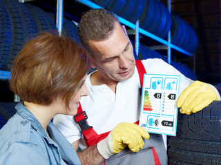 Car mechanic explains to a customer tire labeling in a garage