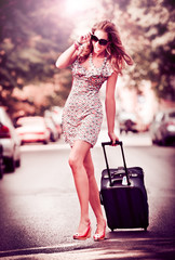 Beautiful woman with suitcases crossing the street in a big city