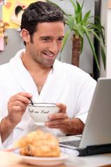 Man having breakfast with computer