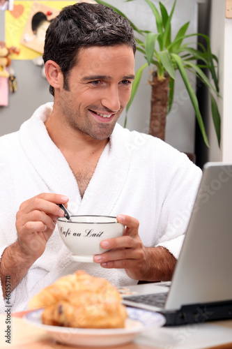 Man having breakfast with computer