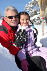 Grandfather and little girl in ski holidays