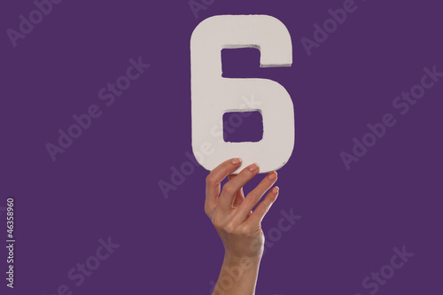 Female hand holding up the number 6 from the bottom