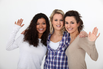 Three female friends waving