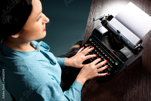 Young woman typing with old typewriter