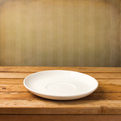 Empty white plate on wooden table over grunge striped wallpaper