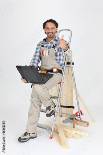 Carpenter sitting on a stepladder with a laptop computer