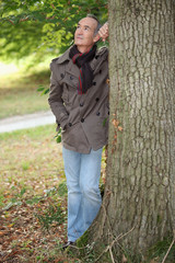 Elderly man leaning against tree