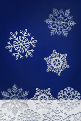 Dark blue winter background with snowflakes falling down