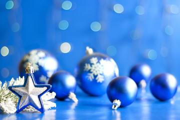 Christmas star closeup and baubles on blue blurred background