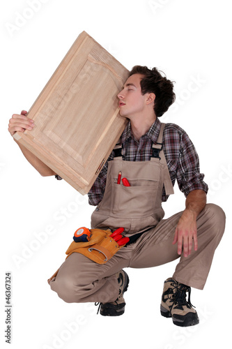 carpenter holding a wooden window