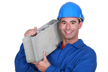 Artisan with concrete block on shoulder