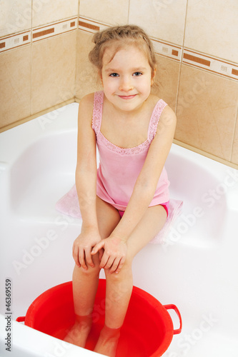 Girl holding his feet in cold water. Harden