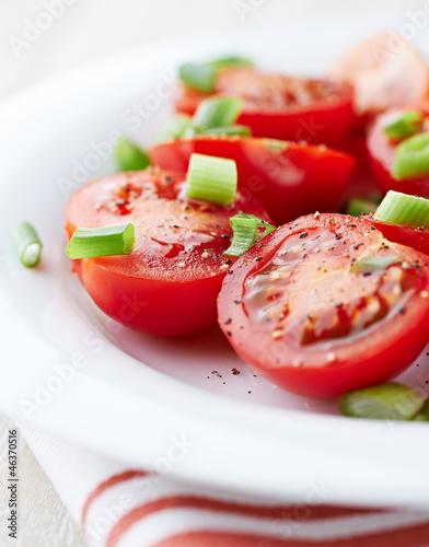 Cherry tomatoes with spring onion on a plate