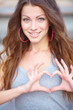 Young beautiful woman show love sign