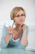 Blond woman holding various prescription drugs