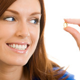 Cheerful woman with Omega 3 fish oil, over white