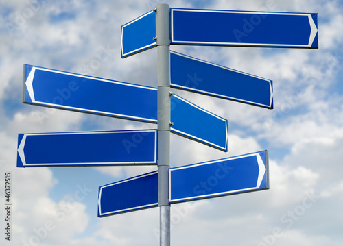 Blank blue direction sign with 8 arrows isolated on sky