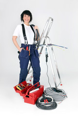 Female electrician stood by ladder