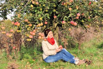 Frau genießt den Herbst unterm Apfelbaum