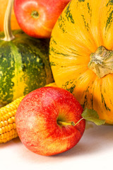apples, pumpkins, corn on a wooden board