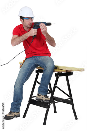 Worker aiming his power drill