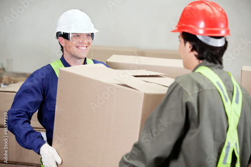 Foremen Carrying Cardboard Box At Warehouse
