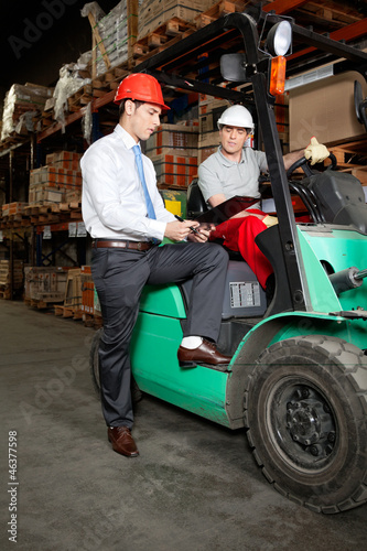 Supervisor Showing Clipboard To Forklift Driver