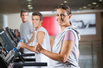 Woman And Men Running On Treadmill In Fitness Center