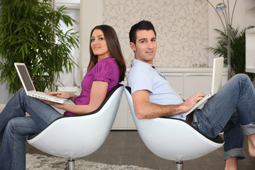 Couple in living room using laptops