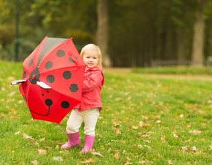 Happy baby playing with red umbrella outdoors