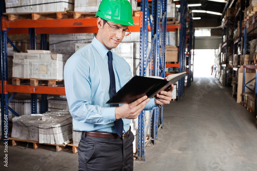 Supervisor Reading Book At Warehouse