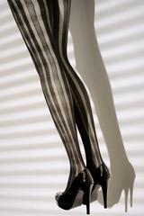 Piernas con medias a rayas y zapatos de tacón