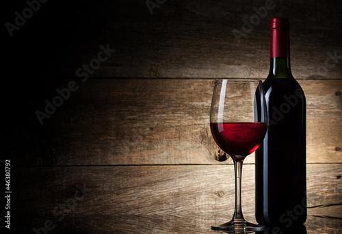 Leinwandbild Motiv Wine glass and Bottle on a wooden background