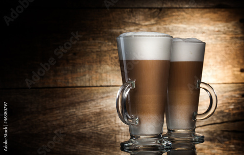 Fragrant coffee latte in glass cups on wooden  background