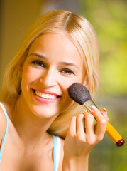 Young blond woman with makeup brush at home