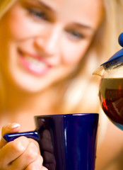 Happy girl with teapot and cup, at home