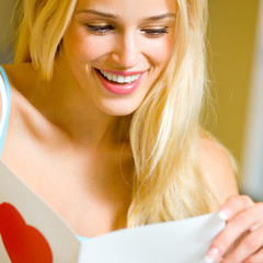 Happy blond woman with valentine card, at home